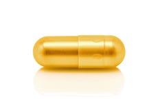 Capsule de pilule d'or sur le fond blanc Images stock