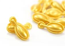 Capsule del cosmetico dell'oro Fotografia Stock
