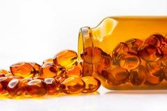 Capsule dell'olio di pesce dalla bottiglia di vetro su fondo bianco Immagine Stock