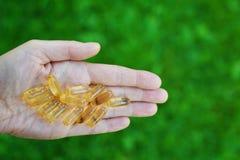 Capsule dell'olio di pesce della tenuta della mano immagine stock