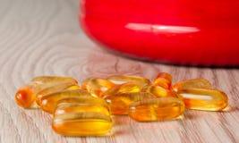 capsule dell'olio di pesce nella forma su fondo di legno immagine stock libera da diritti