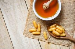 Capsule della pappa reale in cucchiaio di legno sul fondo e sul miele del sacco in tazza fotografia stock libera da diritti