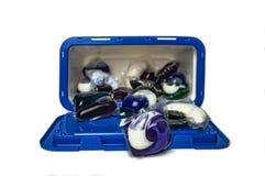 Capsule di gel colorate per lavare in un recipiente di plastica su un primo piano bianco del fondo fotografia stock libera da diritti