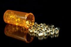 Capsule di gel molli che straripano la bottiglia di prescrizione su superficie riflettente, fondo nero Fotografia Stock