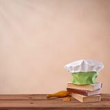 Capsule el cocinero, el libro de cocina y el artículos de cocina en fondo beige del vintage Foto de archivo