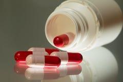 Capsule et bouteille rouges et roses d'antibiotiques photos libres de droits