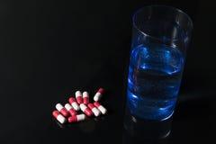 Capsule et verre antibiotiques rouges et roses de l'eau photographie stock libre de droits