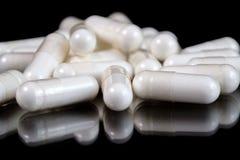 Capsule farmaceutiche oblunghe bianche su superficie riflettente, fondo nero Fotografia Stock