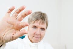 Capsule between fingers Stock Photography