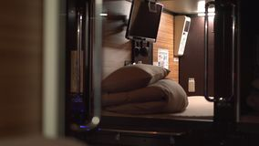 Capsule hotel in Japan, typical design, Inside a pod looking out. POV.  stock footage