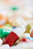 Capsule on medication heap. A red capsule on big medication heap Royalty Free Stock Photos