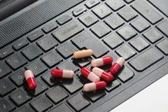 Capsule noire de clavier et d'antibiotiques sur l'ordinateur portable infecté image stock