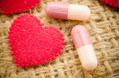 Capsule pill and red heart. Stock Photo