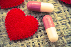 Capsule pill and red heart on sack background. Royalty Free Stock Photos
