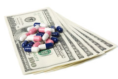 Capsule pills over dollar banknotes isolated Stock Photos