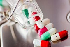 Capsule pills with smile. On reflective surface Royalty Free Stock Photography