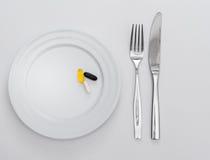 Capsule sul piatto bianco Immagine Stock Libera da Diritti