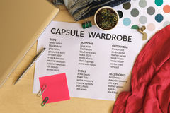 Capsule wardrobe concept. Clothes, laptop and color palette on wooden desk. Flat lay royalty free stock image
