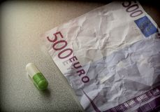 Capsule of white and green on a ticket used 500 euros,. Conceptual image Royalty Free Stock Photos