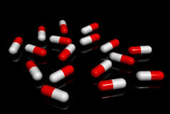Capsules. Red white capsules on a black background Royalty Free Stock Photography