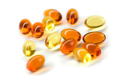 Capsules. Golden and red capsules on white Royalty Free Stock Photo