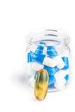 Capsules blanches bleues dans le récipient avec la pilule jaune Photographie stock libre de droits