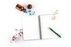 Capsules and bottle with notebook and pen, prescription Royalty Free Stock Image