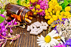 Capsules in brown jar with flowers on board Royalty Free Stock Images