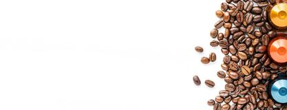 Capsules of Coffee and coffee beans on a white background. Capsules of Coffee placed on a bed of coffee beans on a white background Stock Image