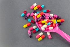 Capsules colorées de médecine avec la cuillère Images libres de droits