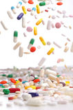 Capsules of colorful remedies falling. Royalty Free Stock Image