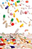 Capsules of colorful remedies falling. Stock Photo