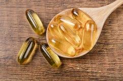 Capsules d'huile de poisson avec Omega 3 et vitamine D dans une cuillère en bois Photo stock