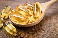 Capsules d'huile de poisson avec Omega 3 et vitamine D dans une cuillère en bois Photos libres de droits