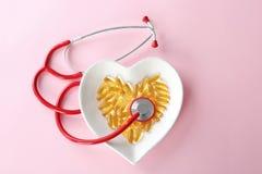Capsules d'huile de poisson dans le plat en forme de coeur avec le stéthoscope images libres de droits