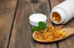 Capsules d'huile de poisson dans une cuillère Images stock