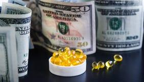Capsules d'huile de poisson et de dollars sur le fond noir Photographie stock libre de droits