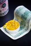Capsules d'huile de poisson et de dollars sur le fond noir Images libres de droits