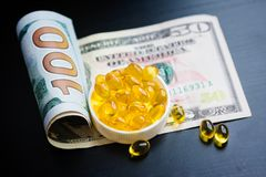 Capsules d'huile de poisson et de dollars sur le fond noir Image stock