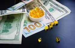 Capsules d'huile de poisson et de dollars sur le fond noir Image libre de droits