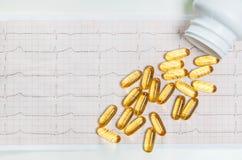 Capsules d'huile de poisson sur le cardiogramme ECG, concept sain de coeur Image libre de droits