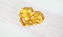 Capsules d'huile de poisson sur le cardiogramme ECG, concept sain de coeur Image stock