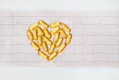 Capsules d'huile de poisson sur le cardiogramme ECG, concept sain de coeur Photographie stock