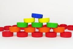 Capsules en plastique colorées, alignées en pyramide en avant du r Photographie stock libre de droits