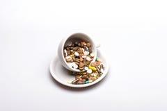 Capsules et comprimés médicaux à l'intérieur de tasse de café Photo stock