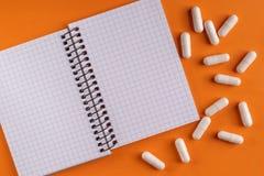 Capsules et pilules médicinales de médecine autour d'un bloc-notes vide sur un fond orange, plan rapproché images stock