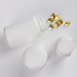 Capsules of fish oil spilled out open container on Stock Photo