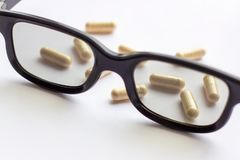 Capsules with glasses on light background. Pharmacy and medicine for eyes concept. Capsules with glasses on light background. Pharmacy and medicine concept royalty free stock photography
