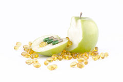 CAPSULES AND GREEN APPLE. Three capsules on a sliced green apple on white background with gold capsules stock photography