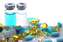 Capsules and Injections. Blue, yellow and red gelatin capsules, glass vials, and syringes Stock Image